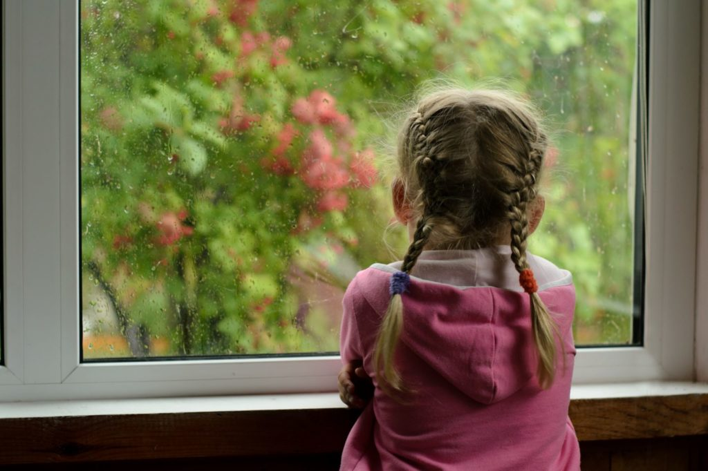 A sad girl looks out the window due to social distancing during virus epidemic.